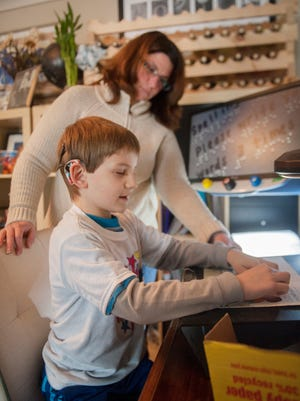 Kim Norton watches as her 7-year-old son Henry Norton, who has limited vision, reads Braille as Henry does his Braille homework in their Mount Laurel home. 02.24.15