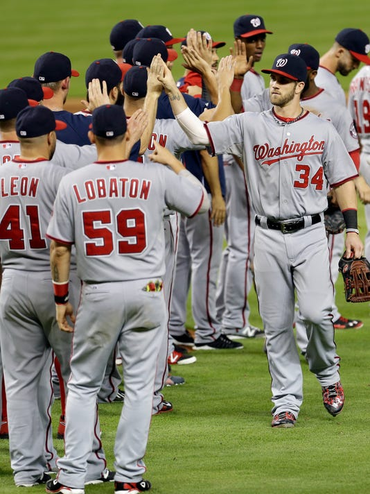 Washington Nationals left fielder Bryce Harper (34) celebrates a 3-2 win with teammates at the end of a baseball game against the Miami Marlins in Miami, Friday, Sept. 19, 2014. (AP Photo/Alan Diaz)