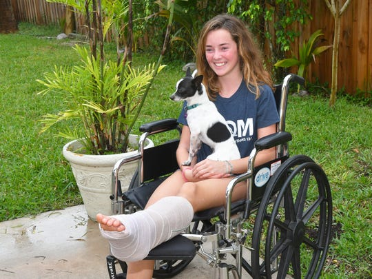 Kaia Anderson, 14, of Floridana Beach (south of Melbourne Beach) was bitten by a shark this past Saturday while surfing. While being interviewed, their dog Spot wanted to be in the photo.