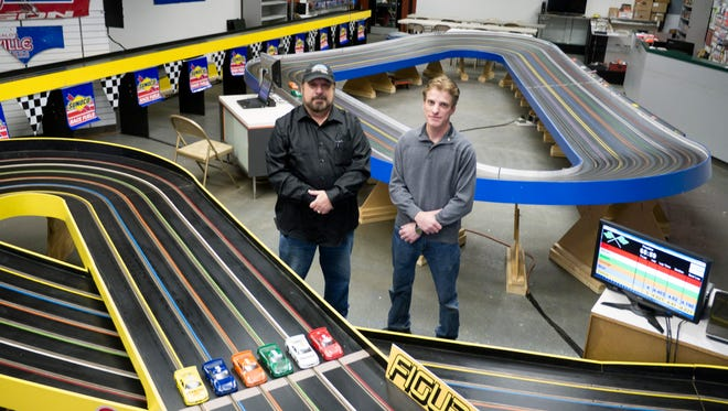 Russell Schmidt and A.J. Marshall pose in their newly opened Staunton Speedway & Hobbies in the Staunton Mall Thursday, Feb. 11, 2016. They are standing between a figure 8 slot car track Schmidt built in the 1980's  and a larger tri-oval.