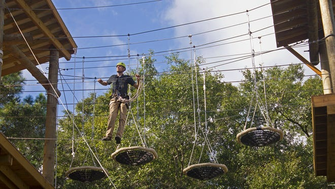 """FSU Campus Recreation staff member Travis Johnson maneuvers through the High Challenge Course obstacle known as """"Basket Case"""" at the FSU Reservation on Monday. The Challenge Course has a grand opening Thursday at 3 p.m."""