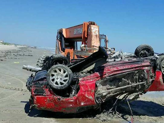 A red Honda Prelude is removed from the beach by a