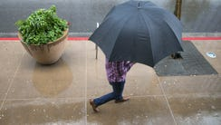 A man tries to stay dry under an umbrella while walking