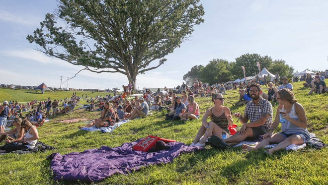 Music fans (from left) Stacey Tucker, Tom Mroz, both of West Des Moines, and Annie Mroz of Johnston find a nice spot on the hillside for Hinterland on Friday, Aug. 5, 2016, in St. Charles.