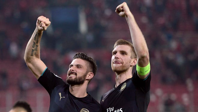 Arsenal's Olivier Giroud (left) and defender Per Mertesacker (right) celebrate match against Olympiakos.
