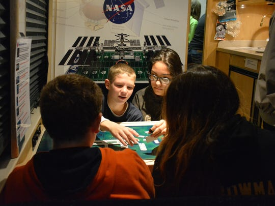 Kewaunee seventh-graders Austin Veesar and Vanessa Guillen work on making a space station prototype with Anthony Tolan and Amber Bowman on the Dream Flight USA Shuttle on Nov. 11.