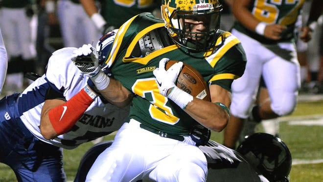 Mayfield's Ethan Alvarado drags a Deming defender during first quarter action on Friday night at the Field of Dreams.