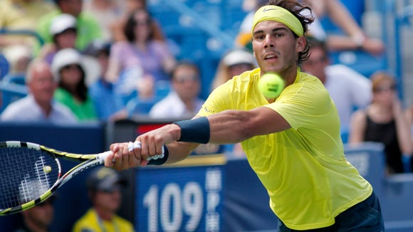 Rafael Nadal returns the ball against John Isner during last year's men's singles final at the Western & Southern Open in Mason.