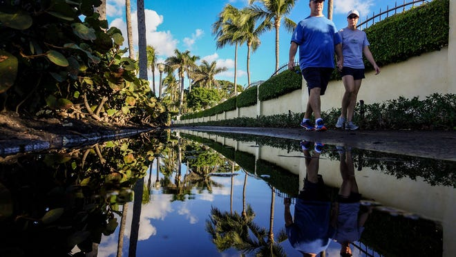 Runners and walkers encounter some sitting water during high tide along the Lake Trail in Palm Beach early Saturday morning on December 2, 2017.