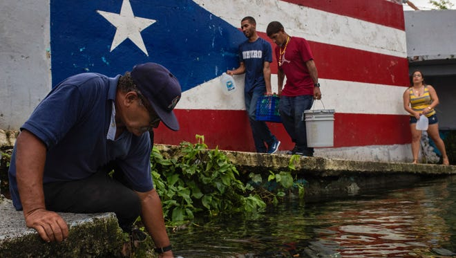 "Residents fill jugs and buckets with water at the ""ojo de aqua,"" or ""eye of water,"" which refers to a natural spring area that creates a water pool, in the Vega Baja municipality of Puerto Rico on Oct. 12, 2017."