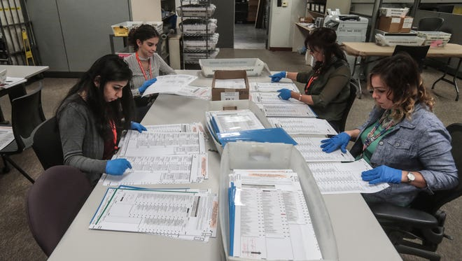 Election workers hand verify mail-in-ballots that vote counting machines have problems reading on Friday, June 1, 2018 at the County of Riverside Registrar of Voters in Riverside.