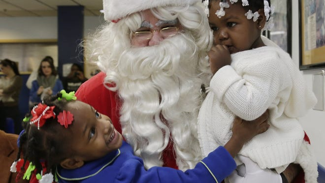 Mariners Inn executive board member Dave Denomme, 52, of Grosse Pointe Woods gets a warm welcome as Santa from Shamyiah Coates, 3, of Detroit, left, and Azaria Scales, 2, of Detroit.