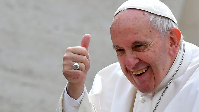 Pope Francis salutes the faithful at the end of his Weekly audience in Saint Peter's square at the Vatican on March 22, 2017.