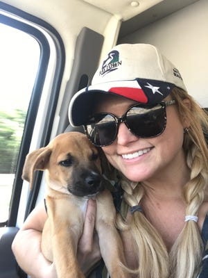 Miranda Lambert cuddles a puppy she and her rescue group MuttNation Foundation saved from a Houston-area animal shelter.