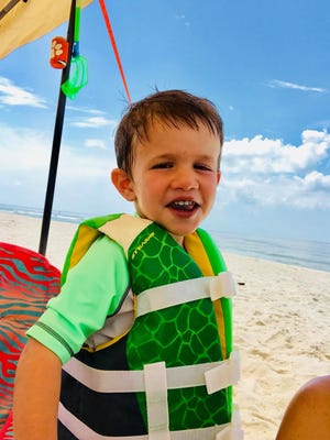 "Levi Hughes, 3, smiles during a sand and sun-filled day on the beach at Fort Morgan, Ala., while on an annual family vacation in June 2018. Levi later drown in the beach-house pool. His death has inspired Tennessee mom Nicole Hughes to create ""water guardian"" tags to remember her son and remind adults to stay alert when kids are around water -- even during times when they are not swimming."