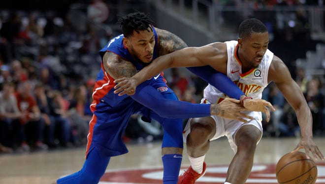 Pistons forward Eric Moreland, left, tries to steal the ball from Hawks guard Isaiah Taylor, right, during the second half on Thursday.