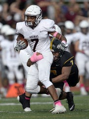Aquinas' Caron Robinson, left, is tackled from behind