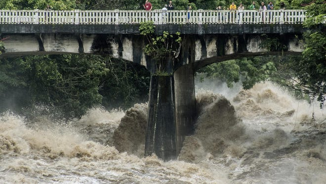 In this photo taken Thursday, Aug. 23, 2018, people look over the Wainaku Street bridge as Wailuku River rages below them in Hilo, Hawaii. Hurricane Lane barreled toward Hawaii on Friday, dumping torrential rains that inundated the Big Island's main city as people elsewhere stocked up on supplies and piled sandbags to shield oceanfront businesses against the increasingly violent surf. The city of Hilo, population 43,000, was flooded with waist-high water.