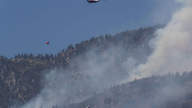 Two helicopters make water drops in the higher elevations of the San Bernardino National Forest during the Apple Fire north of Banning, Ca., August 3, 2020.