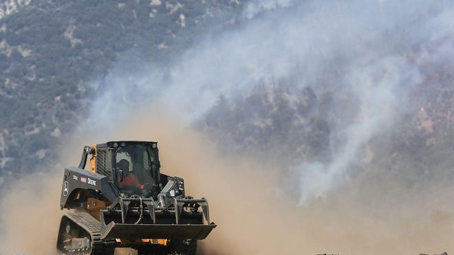 A tractor is used to clear the land near a remote neighborhood near the end of Bluff St. as the Apple Fire continues to burn in the San Berardino Mountains north of Banning, Ca., August 3, 2020.