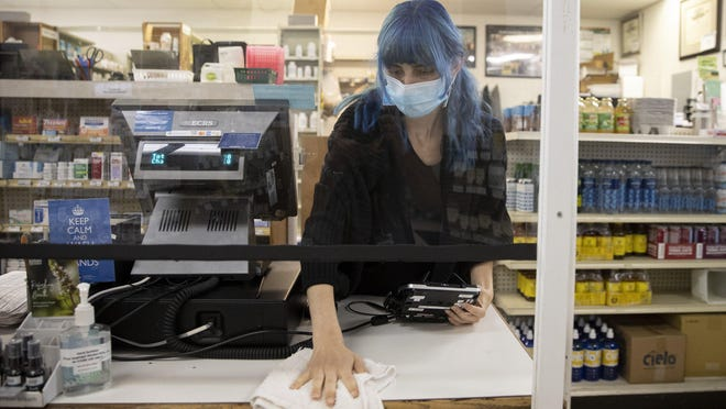 Pharmacy technician Carissa Holmes disinfects the checkout counter at a Peoples Rx on Thursday.