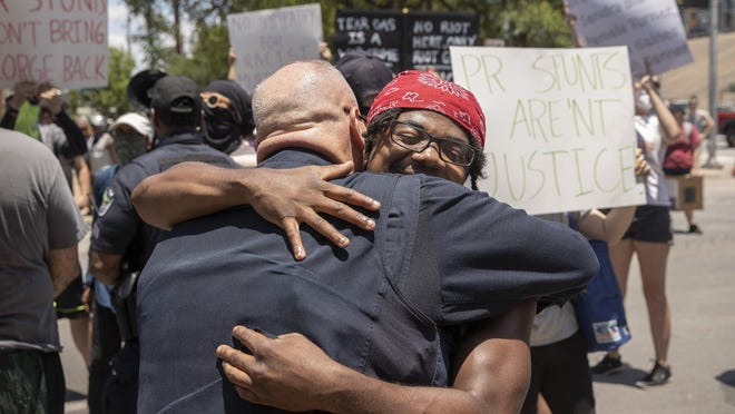 Protester Christian Baker hugs Austin Police Sgt. Michael Crumrine on June 6 after they talked at an event where officers and some protesters knelt in memory of George Floyd.