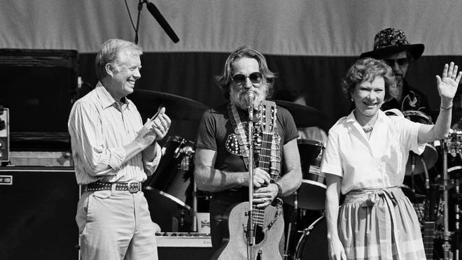 """Willie Nelson, center, is shown on stage with former President Jimmy Carter and his wife Rosalynn Carter, following the singing of """"Amazing Grace,"""" May 18, 1985 in Plains Ga. at Nelson's Plains Centennial Concert."""