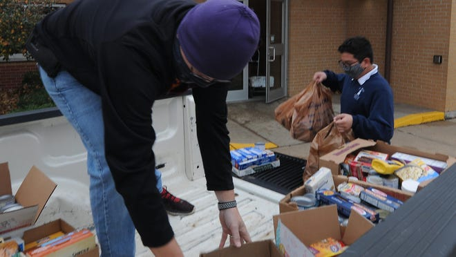 """Doug Patterson, St. Mary's Grade School maintenance director, moves donated food items to the front of the truck bed as fifth-grader Tyler Penn leaves some sacks food on the tailgate after the St. Mary's Grade School surpassed their goal of collecting over 1,000 for the Salina Emergency Aid Food Bank and Catholic Charities of Northern Kansas on Tuesday morning. """"This is the largest food drive we have ever had collecting 1328 items. It is amazing the our families are willing to give back to the community even in such challenging times,"""" said principal Nick Compagnone."""