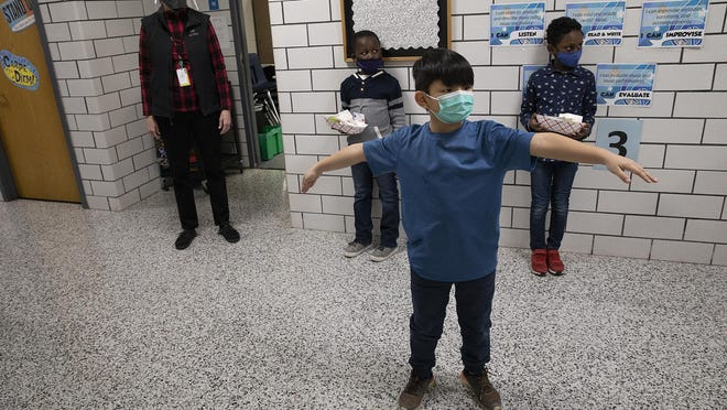 Second grader Cody Yang spreads out his arms as he practices social distancing while standing in the hallway Jan. 19 at Park Brook Elementary School in Brooklyn Park, Minn.
