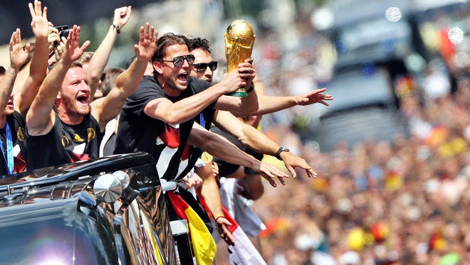 German national football team players cheer as they ride in an open-deck bus to Berlin's landmark Brandenburg Gate to celebrate their FIFA World Cup title.