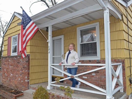 Marlene Nardone stands on the porch of her new home