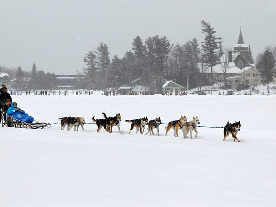This Jan. 30, 2015, photo shows John Houghton, of Vermontville, N.Y., and his sled dog team, giving a ride to a couple, in a snow fall, around Mirror Lake in Lake Placid, N.Y.