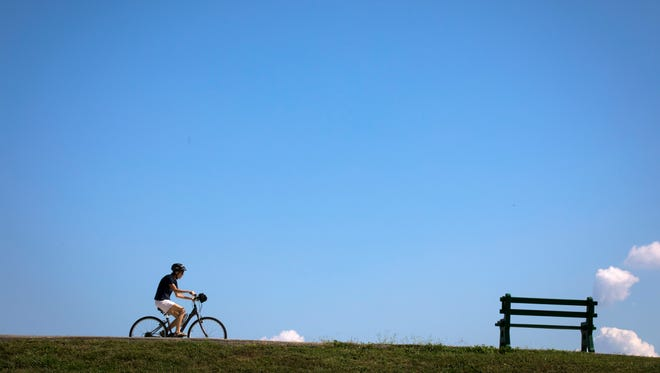 Tues., Sept. 26, 2017: A man rides his bicycle near the Ohio River Trail Farmer's Market trailhead at Wilmer Avenue and Airport Road near Lunken Airport.