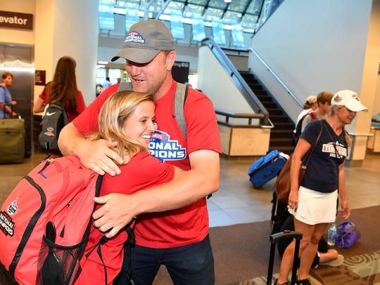 Coach Kyle Roeleke gets a hug from Julie Garst as members
