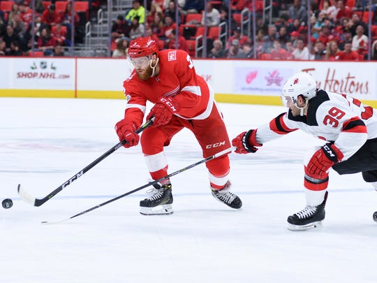 Detroit Red Wings defenseman Nick Jensen (3) clears the puck past New Jersey Devils left wing Brian Gibbons (39) during the second period at Little Caesars Arena on Saturday, Nov. 25, 2017.