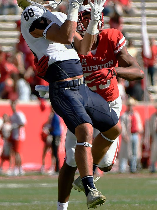 Navy wide receiver Tyler Carmona (88) catches a pass over Houston safety Terrell Williams during the first half of an NCAA college football game, Friday, Nov. 24, 2017, in Houston. (AP Photo/Eric Christian Smith)