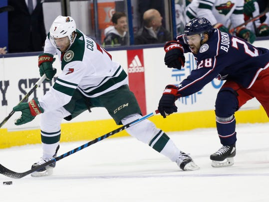 Minnesota Wild's Matt Cullen, left, carries the puck up ice as Columbus Blue Jackets' Oliver Bjorkstrand, of Denmark, defends during the first period of an NHL hockey game Tuesday, Jan. 30, 2018, in Columbus, Ohio. (AP Photo/Jay LaPrete)