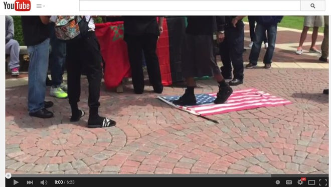 A former U.S. vet was handcuffed after refusing to give up a flag that protesters were walking on.