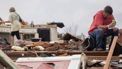 Jeff Bullard sits in what used to be the foyer of his home as his daughter, Jenny Bullard, looks through debris at their home that was damaged by a tornado on Jan. 22, 2017 in Adel, Ga. The severe weather outbreak killed 24 people and caused $1.1 billion in damages.
