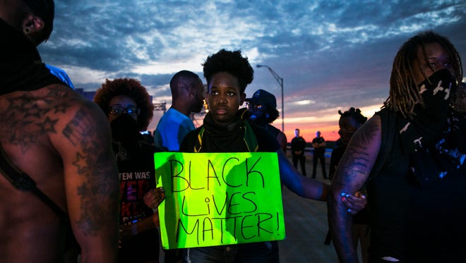 """July 10, 2016 - Community organizer Jayanni Webster (center), 26, stands on the I-40 bridge during a Black Lives Matter demonstration on Sunday. Webster said it was obvious to her on the bridge during the protest that people had their own """"very personal and traumatic experiences of abuse by Memphis police."""" """"Darrius Stewart's murder was a loud hurtful reminder that this is not just about national news, but our own city has to reckon with police terrorism locally,"""" she said. """"Many of us out there on the bridge have been calling for justice for Darrius for the past year. The result was no indictment and retirement for a murderous cop."""""""
