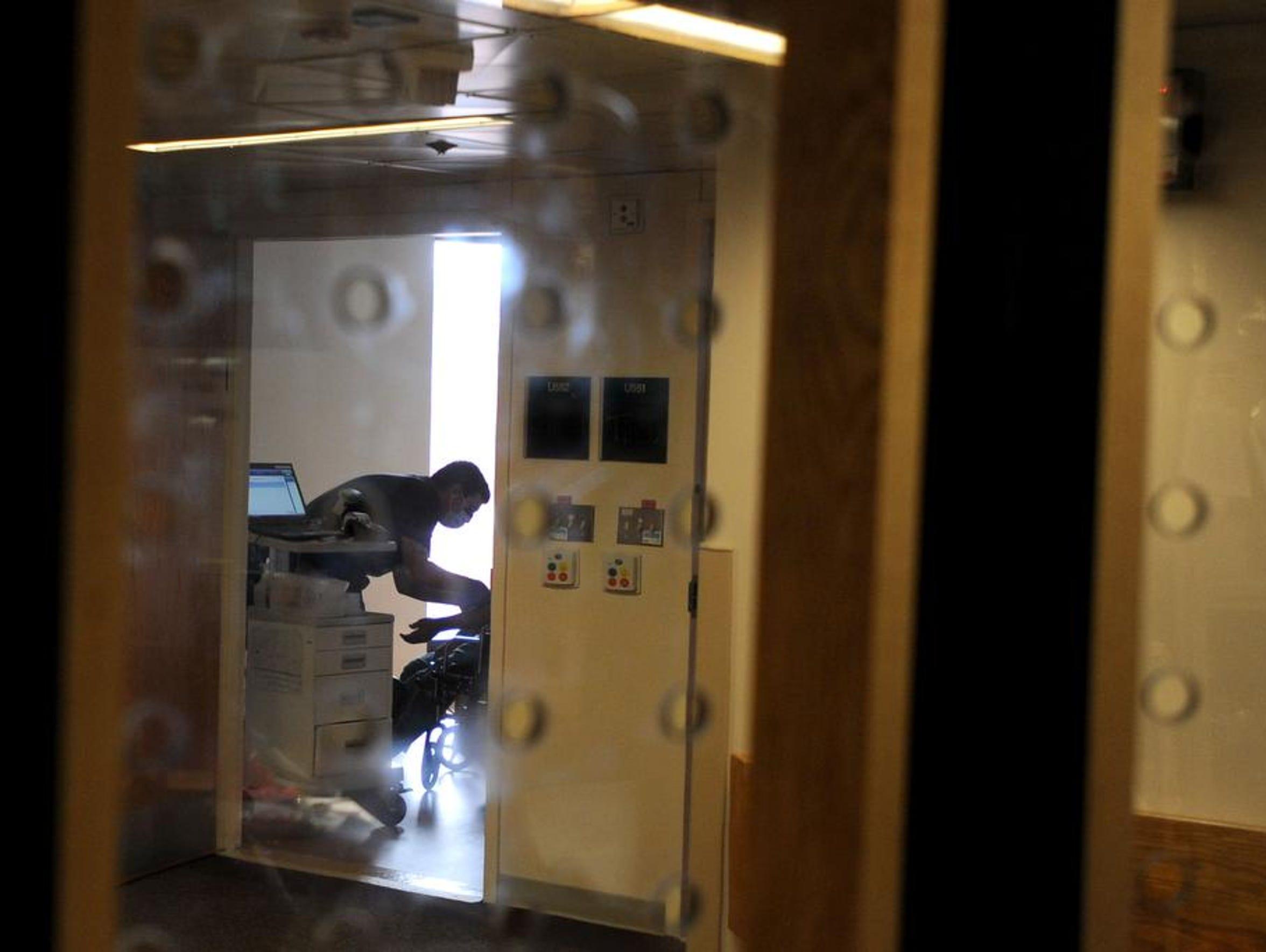 Seem through protective glass, a medical technician