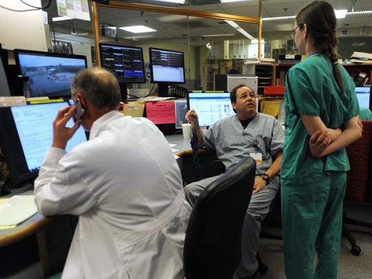 """Dr. William """"Billy"""" Lewis, center, coordinates care with other staff while working in Mission Hospital's Emergency Department."""