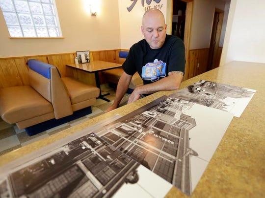 Michael Wirz, owner of Al's Hamburger on Washington Street in Green Bay, looks over historic photos of the restaurant.