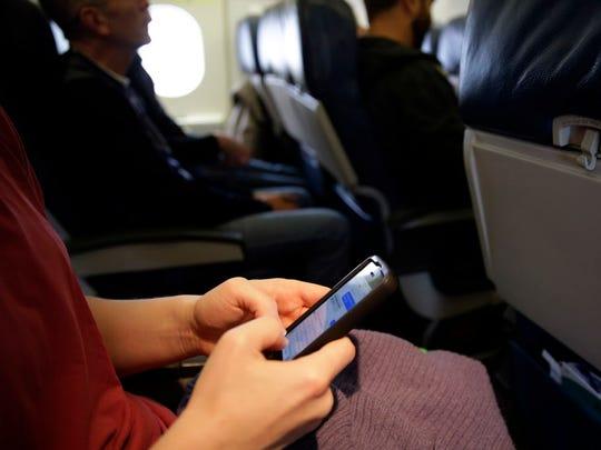 A passenger checks her cellphone Oct. 31, 2013, before