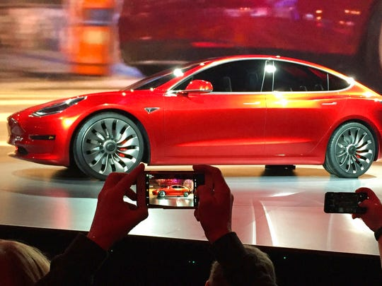 In this March 31, 2016, file photo, Tesla Motors unveils the new lower-priced Model 3 sedan at the Tesla Motors design studio in Hawthorne, Calif.