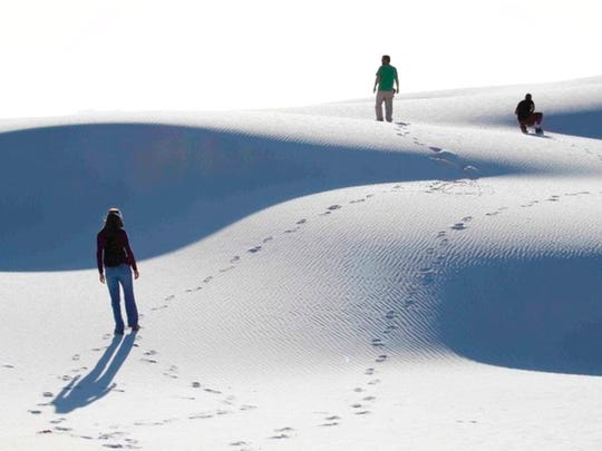 This March 19, 2011 photo shows visitors hiking the shifting dunes of White Sands National Monument . The monument was designated a national park on Friday, Dec. 20, 2019.