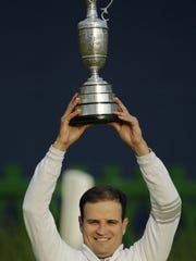 Zach Johnson poses with the trophy after winning a