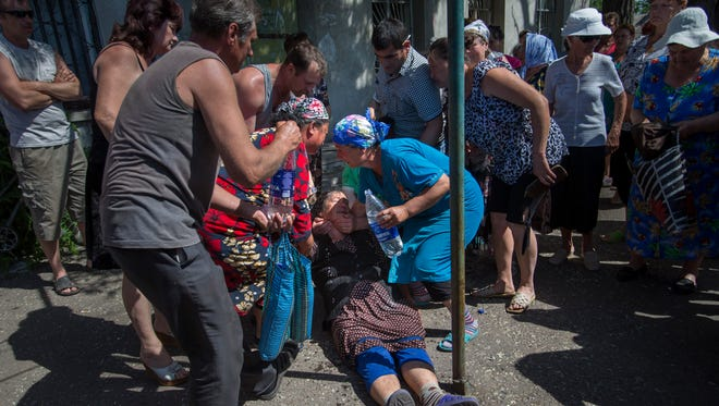 Citizens help a lady who fainted while attending a rally in protest against a shelling by Ukrainian government forces in the village of Semyonovka, Ukraine, on May 22.