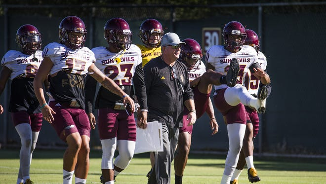 Arizona State head coach Todd Graham walks with defensive players during warmups at practice in Tempe, Wednesday, September 14, 2016.