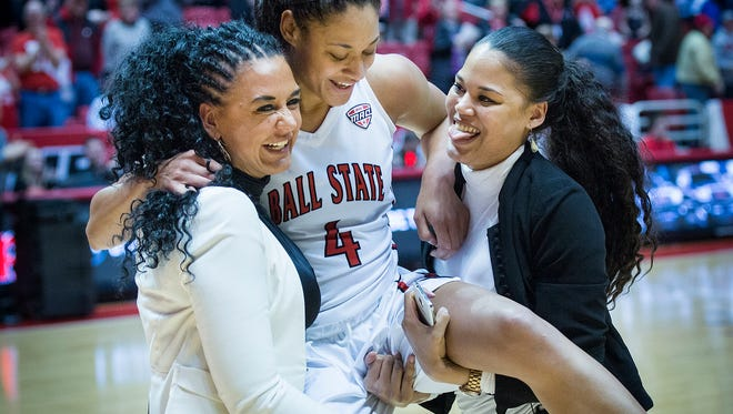 Ball State's Nathalie Fontaine is joined by her mother and sister who try (and fail) to carry her after Fontaine broke the school's all-time scoring record during their game against Northern Illinois Wednesday, March 2, 2016.